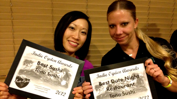 Tina and staff Haley holding the Best Sushi and Best Date Night Restaurant Awards.